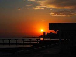 The sun sets in the sky over the sea with the silhouettes of the pier and other structures. Sunset over the sea