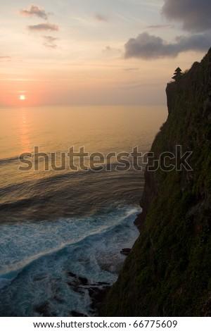 The sun sets on a Hindu temple beautifully set on cliffs overlooking the ocean in Uluwatu, Bali, Indonesia