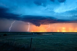 The sun sets on a lighting storm on the Great Plains