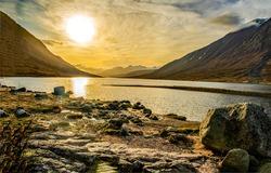 The sun sets over a mountain lake. Mountain lake at sunset. Lake in mountains at sunset. Sunset over lake in mountains