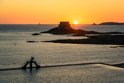 The sun setting behind the tidal island Petit Be, in front of the walled city of Saint Malo in Brittany, France, with the tidal pool of the Bon Secours beach and its diving platform in the foreground.