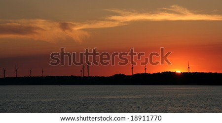 The sun setting just over the horizon with wind turbines in the background.