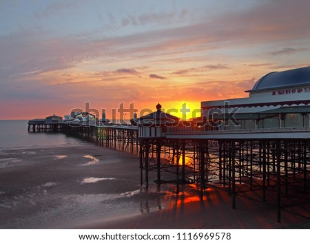 the sun setting over the historic north pier in blackpool with glowing light reflected on the beach and colourful twilight sky #1116969578
