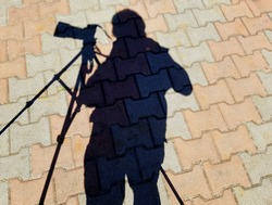 The sun shadow of a photographic tripod, a camera mounted on it and a human figure against the background of paving slabs