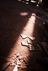 The sun shines from the window and shines on the broken glass on the ground