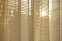 The sun shines through the white organza tulle and blinds
