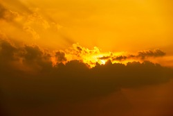The sun shone an orange light that was moving into the black clouds just before sunset.