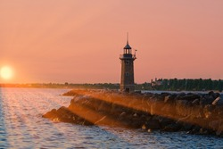 The sun, the sun's rays illuminate the lighthouse early in the morning. The light brick Italian lighthouse in the port of Desenzano del Garda, Lombardy, Italy.