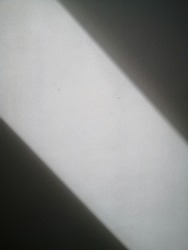 The sunlight shines in diagonal lines on the white plaster wall, creating dark shadows on both sides.