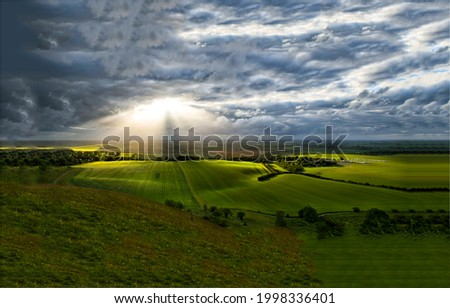 The sunrays break through the storm clouds. Agriculture field above stormy sky clouds. Storm clouds before rain. Agriculture rainy weather