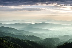 The sunrise shines down the green forest mountain in Myanmar.