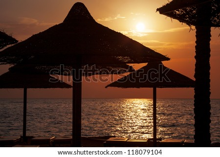 The sunrise through woven sun umbrellas and sun loungers. On the beach overlooking the Red Sea, Sharm el Sheikh.