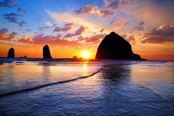 The Sunset at Cannon Beach with Dramatic clouds in the background and a nice reflection