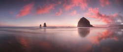 The Sunset at Cannon Beach with Dramatic clouds in the background and a nice reflection in water.  Dramatic coastal seascape featuring scenic rock formations Haystack Rock Oregon, USA