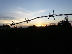 The sunset behind the house, barbed wire at autumn sunset background,Barbed wire and sunset,Light and shadow at sunset