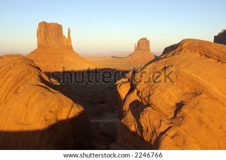 The sunset in Monument Valley (Navajo Nation, Utah). Two mittens are framed by two boulders...