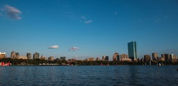The sunset is distinguished in the city of Boston, Massachusetts, United States of America, seen from the river of the city, panoramic photography, the buildings and the sunset are distinguished