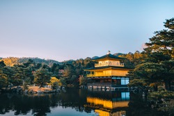 The sunset of golden pavilion building in autumn season, Kinkakuji temple the most famous Asia landmark for travel with tourist, beautiful zen heritage ancient historic temple in Kyoto, Japan