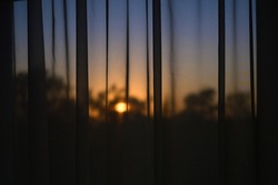 The sunset through the tulle on the window. Contour evening dusk light. Mesh fabric texture with sun glare.