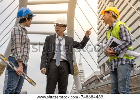 The supervisor is discussing the construction with the Asian staff and the architect at the site