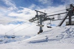The support of the chairlift at the top of the ski resort. Against the background of snow-capped peaks covered with fog. The concept of active winter recreation
