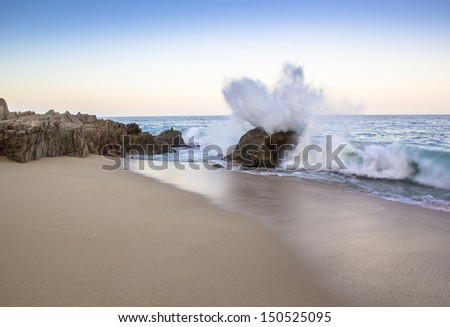 The surf crashes against a rocky seashore.
