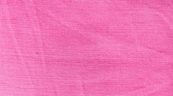 The surface of a light pink natural dyed cotton fabric sheet with wrinkles. The abstract pink fabric background texture for decorating and design.