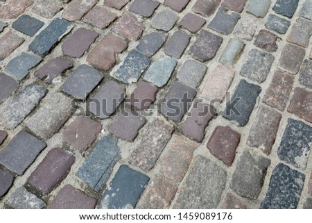 The surface of cobbled street is seen on one of the streets of the old town of Warsaw in Poland.