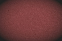The surface of dark brown cardboard. Paper texture with cellulose fibers. Paperboard wallpaper or background with vignetting. Macro