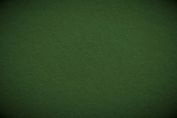 The surface of dark green cardboard. Paper texture with cellulose fibers. Paperboard wallpaper or background with vignetting. Glamorous and elegant autumn color. Macro