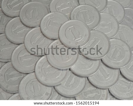 The surface of many Japanese coins in denominations of 1 yen. Gray background or wallpaper. Information about the economy, finance, banks of Japan. Deposits and loans to corporations. Macro #1562015194