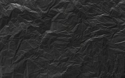 The surface of the black plastic bag is crumpled. Abstract black garbage plastic bag background with a soft focus.