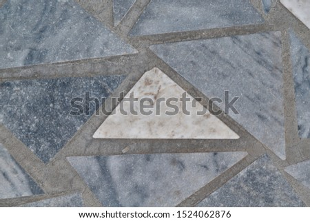 The surface of the triangular marble tiles. In the center of the white triangle, on the edges of the gray triangles. The triangles are arranged in a chaotic order. Background, texture, backdrop. #1524062876