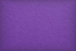 The surface of violet cardboard. Paper texture with cellulose fibers. Bright purple tinted background with vignetting. Dark summer paperboard wallpaper. Saturated color. Top-down. Macro