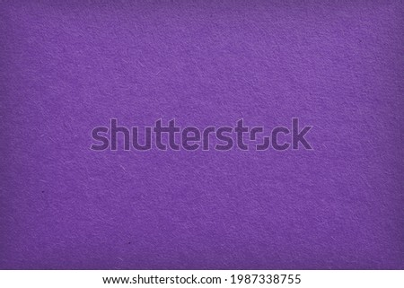 The surface of violet cardboard. Paper texture with cellulose fibers. Bright purple tinted background with vignetting. Dark summer paperboard wallpaper. Saturated color. Top-down. Macro Stockfoto ©