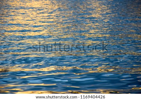 The surface water is golden light reflected from the sun