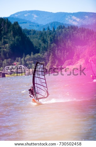 The surfer enjoying a walk with sail under the fresh summer wind along the Columbia River in the picturesque Columbia Gorge in the Hood River - the center of windsurfing as a professional sport.