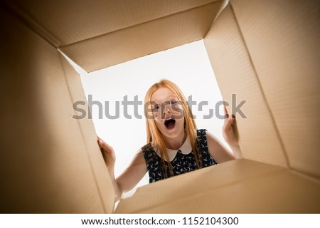 The surprised girl unpacking, opening carton box and looking inside. The package, delivery, surprise, gift lifestyle concept. Human emotions and facial expressions concepts #1152104300