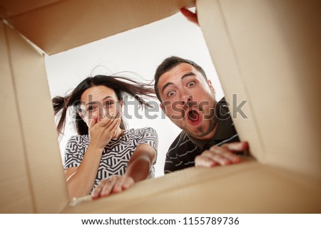 The surprised man and woman unpacking, opening carton box and looking inside. The package, delivery, surprise, gift and lifestyle concept #1155789736