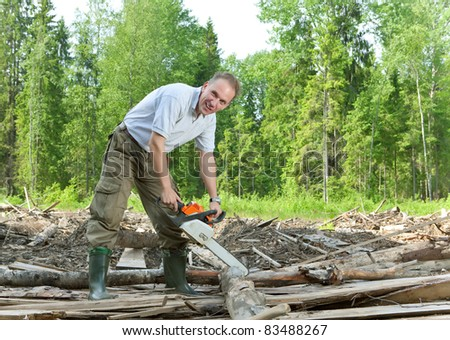 The surprised man with a chain saw in summer wood