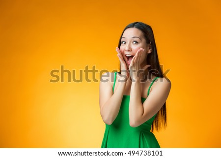 The surprised young Chinese girl on yellow background