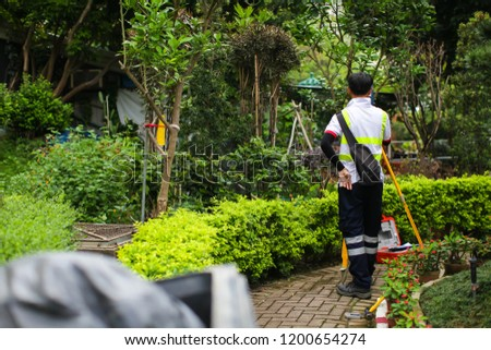 The surveyor makes measurements for the cadastre. Asian surveyor working in green summer park.