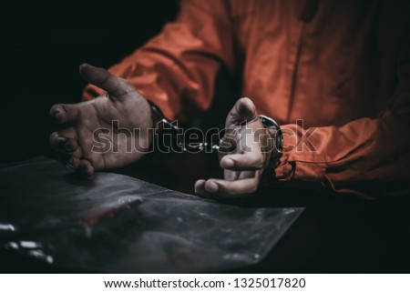 The suspect wear prisoner cloths was arrested at the investigation, interview to find out the truth, the thief was caught by the police come to the dark room,Thailand people,Knife in hand Stock photo ©
