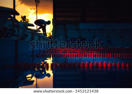 The swimmer jumps from the start block at the start of the race. Swimming sport concept photo. Black edit space #1453121438