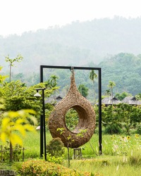 The swings are made of circular rattan in a lush field with mountains and villages as a backdrop.