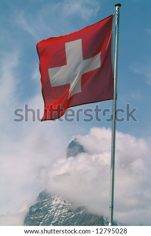 The Swiss flag flying above the Matterhorn peak in Switzerland with cloudy blue sky
