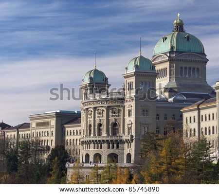 The Swiss parliament building (Bundeshaus) in Bern. Side view shot in autumn with yellow trees in the foreground.