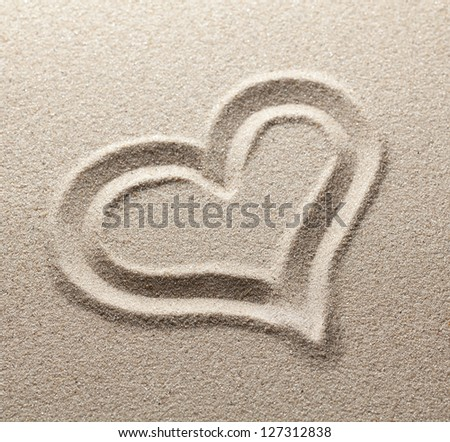 The symbol of heart is drawn on clean sand