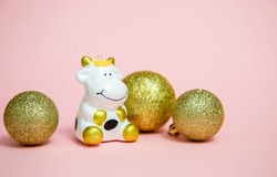 the symbol of 2021 is a white bull according to the Eastern calendar on a pink background in the form of a toy with balls for a tree of gold color. Holidays, winter and celebration concept. Merry Cris