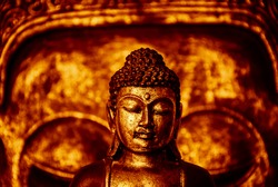 The symbol of the richness, of the founder of Buddhism, Buddha miniature statue sculpture with golden painted wood carved Buddha face on the background, with red effect